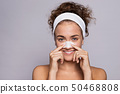 Portrait of a young woman cleaning face in a studio, beauty and skin care. 50468808