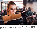 Young girl or woman with gloves, doing exercise in a gym. 50468899
