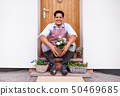A portrait of young man sitting in front of door at home, planting flowers. 50469685