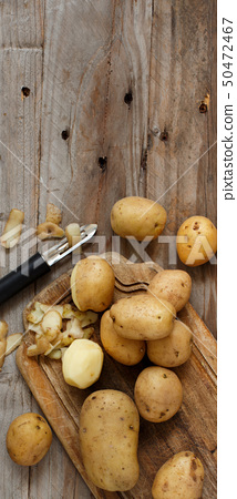Raw potatoes with a vegetable peeler 50472467