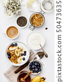 Oat granola with yogurt, honey, fresh bananas, blueberries, chia seeds in bowl and cup of coffee on 50473635