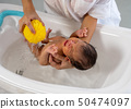 White shirt mother use yellow sponge to bath 50474097