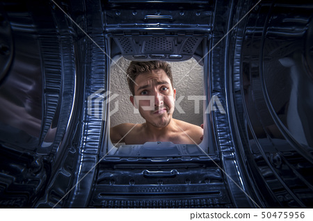 Young man doing laundry View from the inside of broken washing machine 50475956