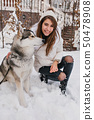 Adorable caucasian woman spending time outdoor enjoying frosty weather with her pet. Photo of pretty 50478908