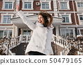 Inspired woman jumping in sunny winter day, enjoying christmas holidays. Outdoor photo of funny 50479165
