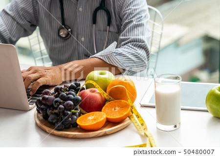 Senior male nutritionist doctor working at desk. 50480007