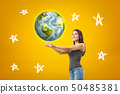 Young smiling brunette girl wearing casual jeans and t-shirt with palms up, earth globe and cartoon 50485381