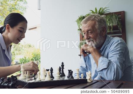 senior man happiness and nurse, playing chess at 50489095