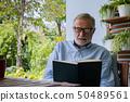senior man happiness sitting and reading book at 50489561