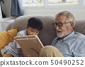 senior man happiness and grandson are sitting on 50490252