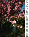 Beautiful woman in sunglasses stand in sakura tree 50493014