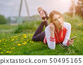 Woman with earphones and smartphone listening to 50495165