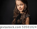 Pretty, little model with long, curly hair posing in studio. 50501024