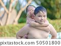 Brother holding his sister on his back in swimming 50501800