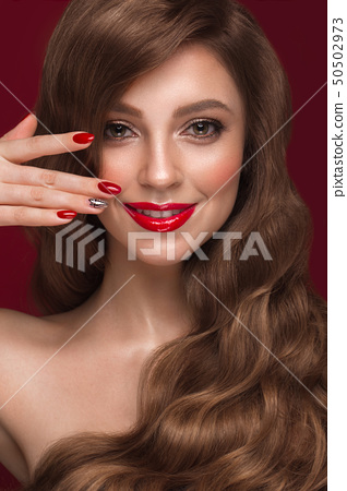 Beautiful girl with a classic makeup, curls hair and red nails. Manicure design. Beauty face. 50502973