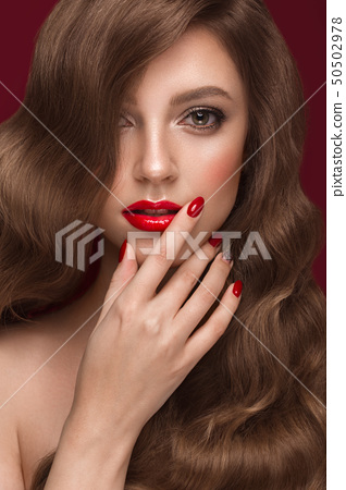 Beautiful girl with a classic makeup, curls hair and red nails. Manicure design. Beauty face. 50502978