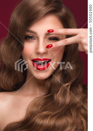 Beautiful girl with a classic makeup, curls hair and red nails. Manicure design. Beauty face. 50502980