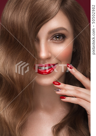 Beautiful girl with a classic makeup, curls hair and red nails. Manicure design. Beauty face. 50502982