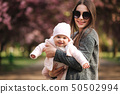 Mom fly with her little baby in tha park. Happy family 50502994