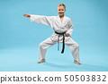 Happy girl in white kimono standing in universal stance 50503832