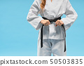 Front view of kimono on little fighter keeping black belt 50503835