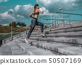 Girl runs in the summer in the city, on morning run. Stair background, blue sky with clouds 50507169