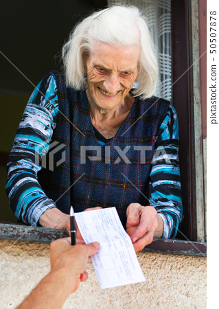 Senior woman receiving retirement check at home 50507878