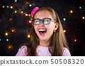 Portrait of cheerful teenage girl on festive 50508320
