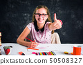 Happy girl drawing with colorful pencils 50508327