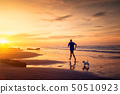 Man and small dog are running at the beach  50510923