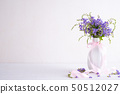 lovely purple flower in vase on white wooden 50512027