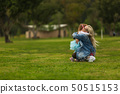 Baby hugging with mom in the park on the green grass 50515153