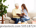 Mother showing daughter photos in album at home 50518724