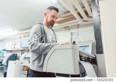 Man preparing large format printer for a print job