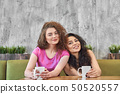 Front view of female friends having breakfast in cafe 50520557