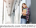 Student girl with books on university background 50520652