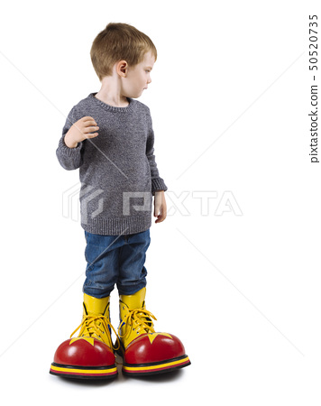 Young boy with big clown shoes 50520735