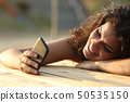 Woman watching social media in a smart phone at 50535150