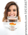 Pet fish in a glass needs care and a woman looking 50535607