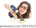 Funny geek girl trying to open a tin with a drill 50535620