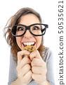 Funny geek girl eating a cookie 50535621