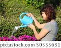 Beautiful woman watering flowers with a watering 50535631