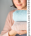 Woman holding clean folded towels 50546484