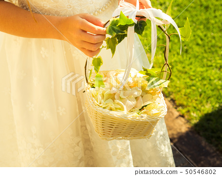 Flower girl in white dress with basket of petals 50546802