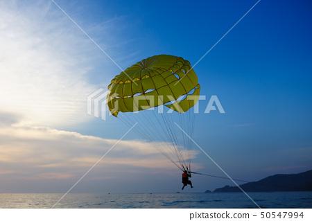 Man parasailing at sunset 50547994