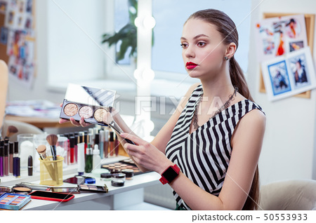 Pleasant beautiful woman holding her powder palette 50553933