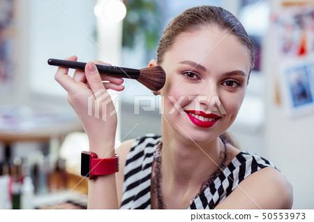 Positive nice woman using her makeup brush 50553973