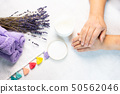 An elderly woman applies the cream on skin of the hands 50562046