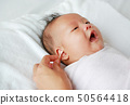 Close-up mother use cotton bud to clean baby ear. 50564418