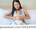 Mom take care infant with pain in her Stomach. 50564446